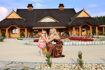 Mama z małą córeczką bawią się przed restauracją.