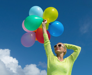 Woman holding balloons against cloud and sky