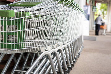 Many empty shopping carts in a row with old shopping femal in ba