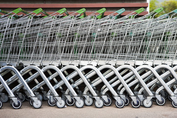 row of shopping trolleys or carts in supermarket