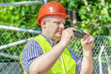 Worker with  sunglasses near the fence
