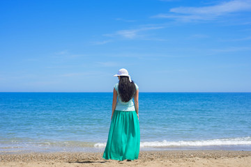 Brunette female standing alone on the beach
