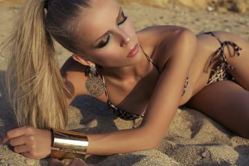 sexy girl with blond hair in bikini lying on beach