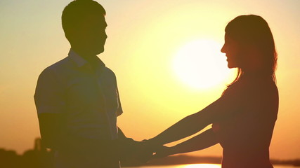 Young couple in love at sunset on the lake, enjoying each other