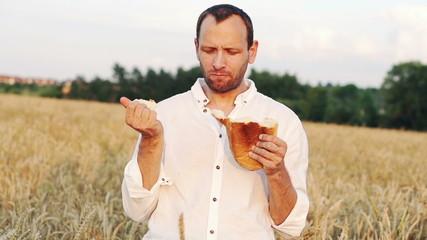 Man eating bread in wheat field, super slow motion, 240fps