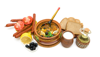 Dish of russian hodgepodge soup in ceramic pot and other foodstu