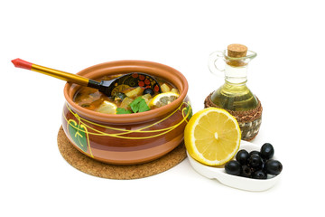 Dish of russian hodgepodge soup in ceramic pot on white backgrou