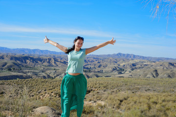 Happy woman open arms stand at mountain
