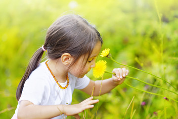 Little girl in the forest smells wonderful flowers and enjoy