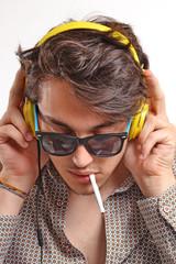 Retrato de un deejay fumando con audífonos amarillo.