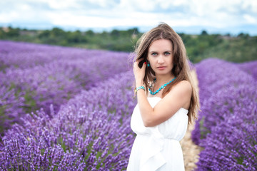 Beautiful girl with green eyes enjoying the scent of lavender