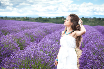 Beautiful girl enjoying the scent of lavender fields