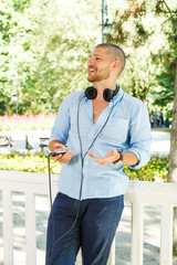 Handsome guy in the light blue shirt posing with headphones
