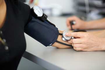 doctor measures the blood pressure of a patient