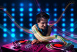 Young Dj mixing records with colorful lights
