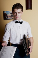 Handsome bartender in uniform with menu.