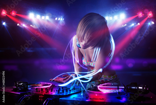 Disc jockey girl playing music with light beam effects on stage - 68023496