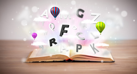 Open book with flying 3d letters on concrete background