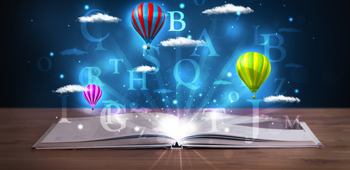 Open book with glowing fantasy abstract clouds and balloons
