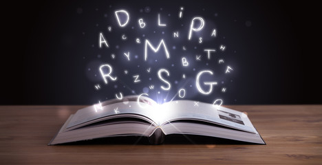 Open book with glowing letters flying out