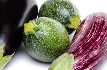 Purple and black eggplant and two zucchini