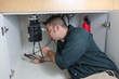 Plumber fixing a garbage disposal - 68026856