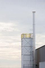 Factory chimney in the white sky