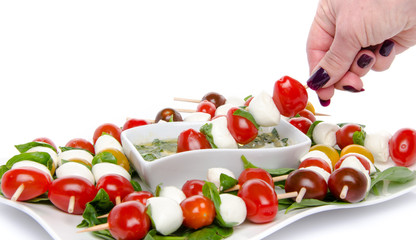 Hand dipping a skewer of cherry tomatoes and mozzarella in a vin