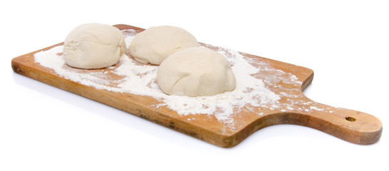 Three balls of pizza dough on a wooden board