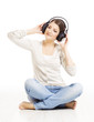 Woman in headphones listening to music on white background