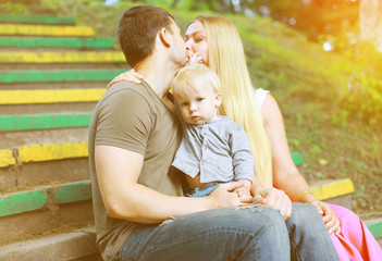 Happy family in  summer day, parents kiss and child