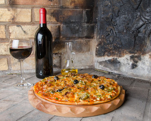 Pizza with wine and oil on a firebricks background