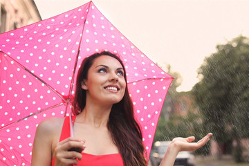 Portrait of beautiful young girl walking with umbrella