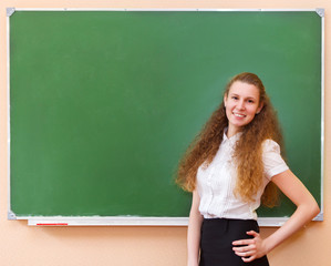 Student girl standing near blackboard