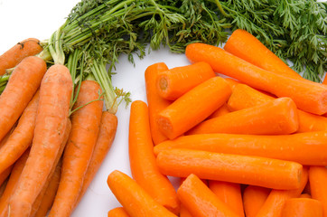 Bunch of fresh carrots and heap of peeled carrots
