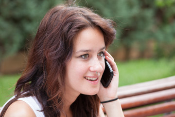 Surprised smiling girl talking on mobile phone. In the park.