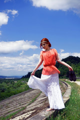 Young redhead walking on a roads edge