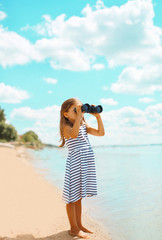 Child looking through binoculars in the expanse of the sea