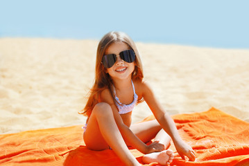 Child has a rest in the summer on the beach