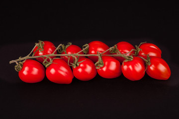 sprig of cherry tomatoes isolated on a black background
