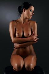 Sexy young woman posing nude with oiled skin