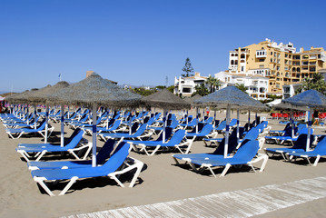 Empty sun loungers on Cabopino beach
