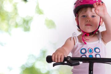 kleines Mädchen mit einem rosa Schutzhelm auf ihren Rad