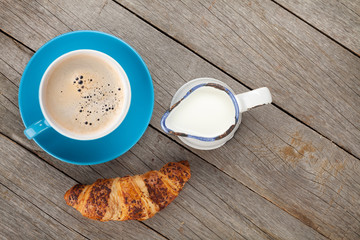 Cup of coffee, milk and fresh croissant