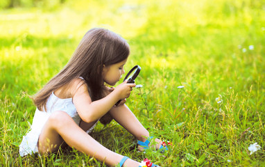 Little girl looking through a magnifying glass on flower
