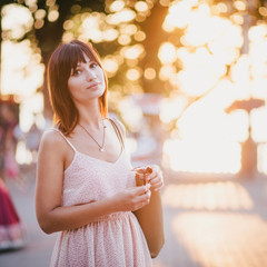Fashion beautiful woman in a pink dress posing at the sunset