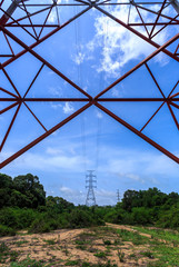 Power pylon with trees and blue sky and white clouds