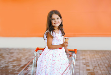 Sweet little girl in shopping cart with icecream