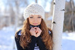 Beautiful brunette in a white hat standing in a park in winter