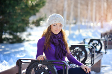 Beautiful and sexy woman sitting on bench in winter